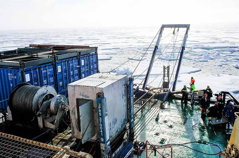 Översikt av arbetet med att borra upp sedimentkärnor, på Odens akterdäck. De upp till 12 m långa och 1,5 ton tunga kolvkärnorna sätts igång med hjälp av en vagga som glider på en skena på akterdäck. Denna nya sjösättningsmetoden installerades just före expedition startade i Landskrona när Oden var i torrdocka. Det visade sig vara utmärkt metod och minskade tiden vid borrstationerna avsevärt i jämförelse med tidigare expeditioner. Foto: Martin Jakobsson.