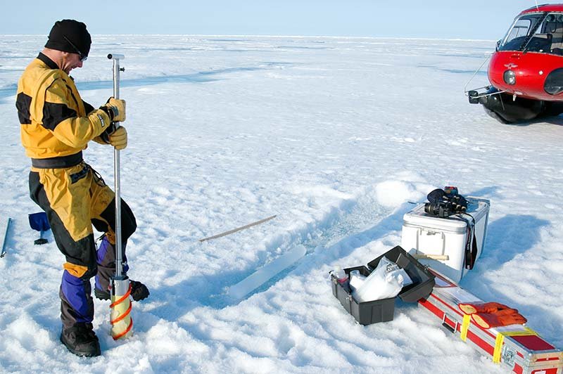 Ice coring procedure. A hand powered KO VACS ice corer was used to create a hole for in situ measurements of CO2 flux and to obtain samples for biological analysis. To prevent contamination, cores were placed in a trench cleared of snow. Pictured: Jeff Bowman. Photo: Matthias Wietz.