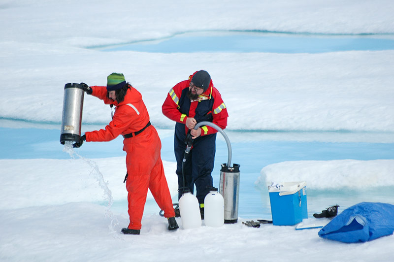 Collecting water samples from a melt water pool on the ice. Photo: Gunnar Kihlberg.
