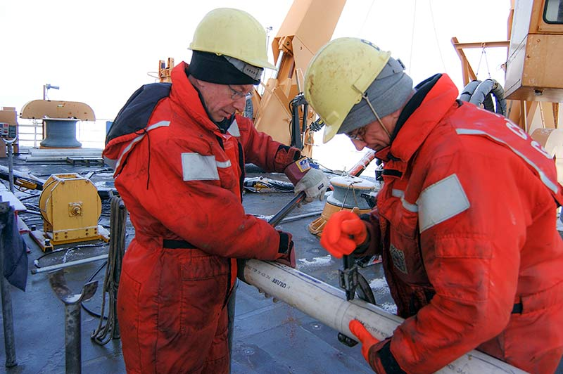 ennis Darby and Reidar Lövlie are handling a piston core section on the Healy icebreaker. Photo: Martin Jakobsson.