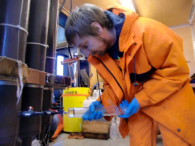 Sören Gutekunst is taking water samples to measure CFC and SF_6 and  (chlorofluorocarbons and sulfur). Photo: Leif Anderson