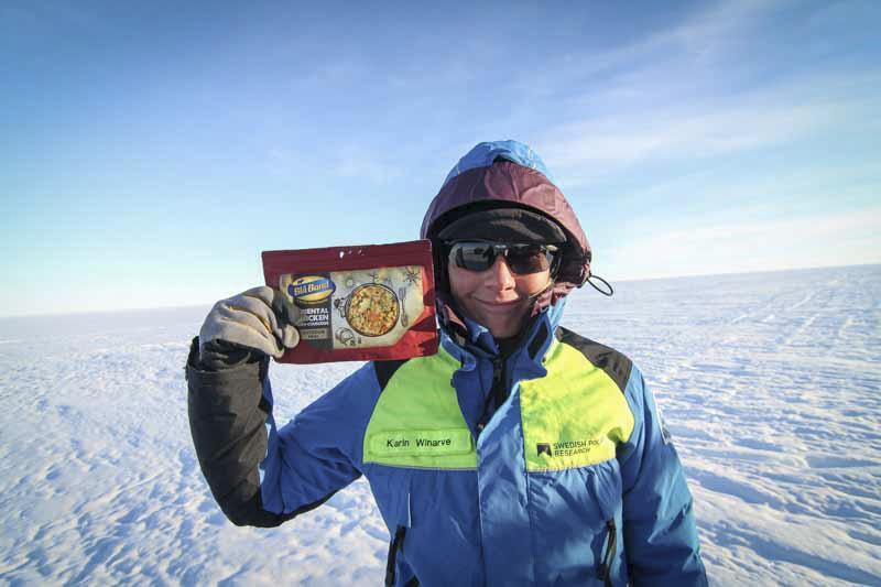 Kvinna i blå jacka håller upp ett paket med frystorkad mat.