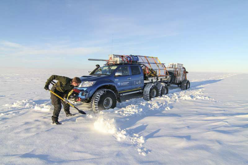 Man skottar snö framför bil