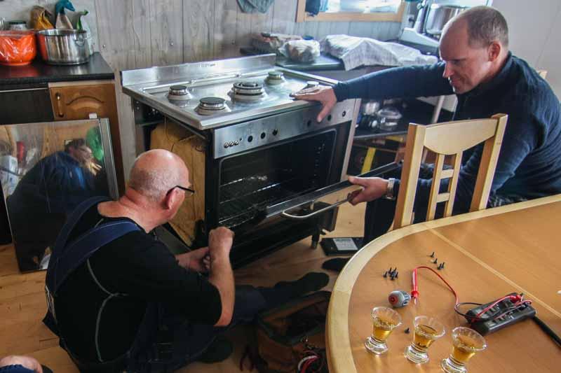 Three men sitting around the stove