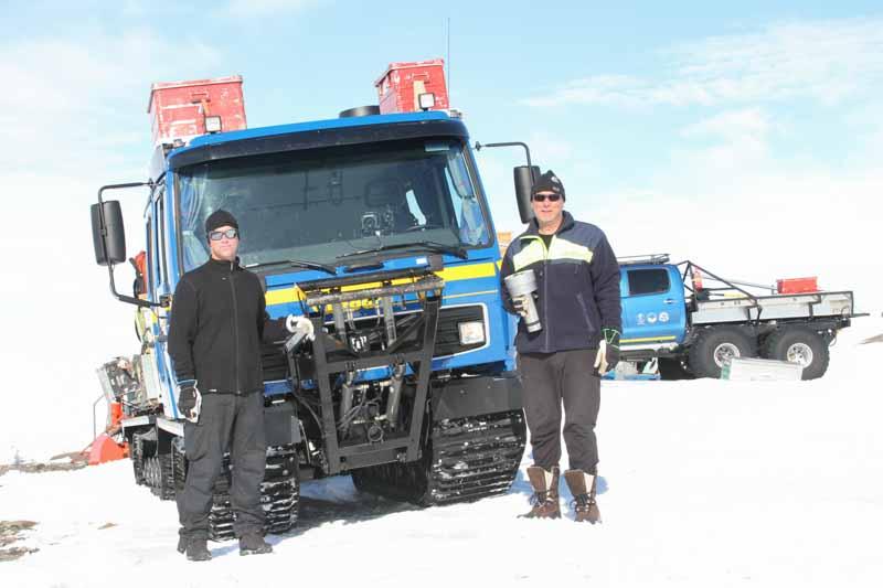 Två män framför en blå bandvagn