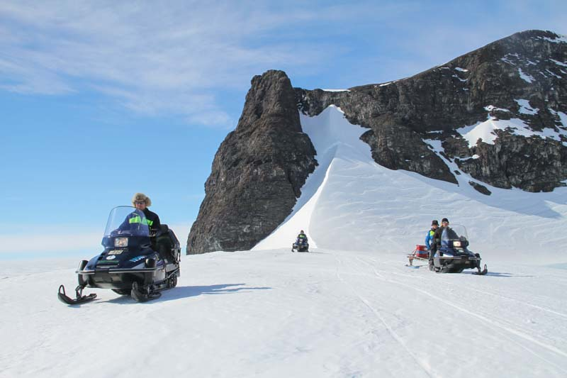 Snowmobiles in front of a mountain