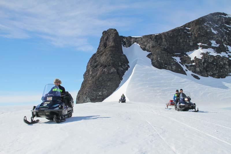 Tre skotrar framför en nunatak