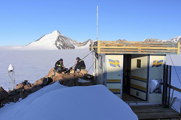 Två personer äter mat bredvid stationen Svea med berg skymtandes i bakgrunden