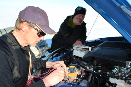 Two men leaning over the car engine