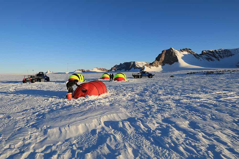 Fältläger bestående av tre tält med berget i bakgrunden.