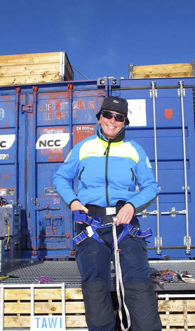 Karin poserar glatt framför en container