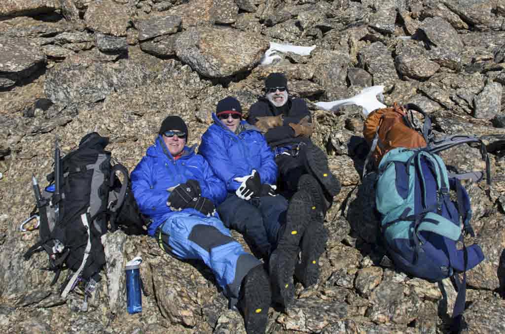 Två män sitter och fryser och den tredje ser glad ut