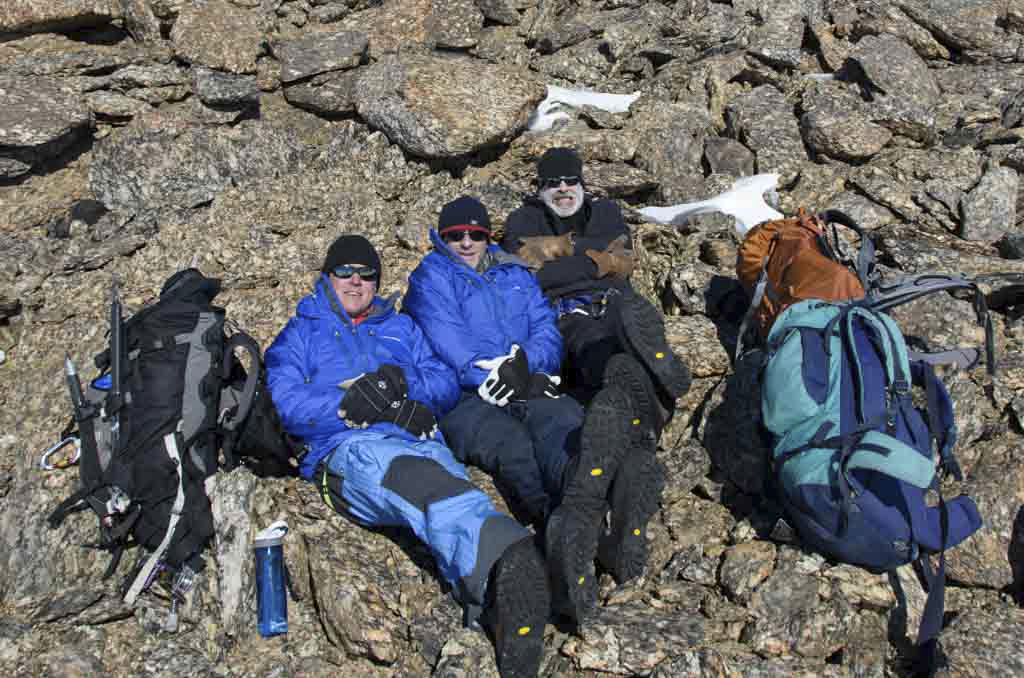 Three men sitting down on boulders in Antarctica