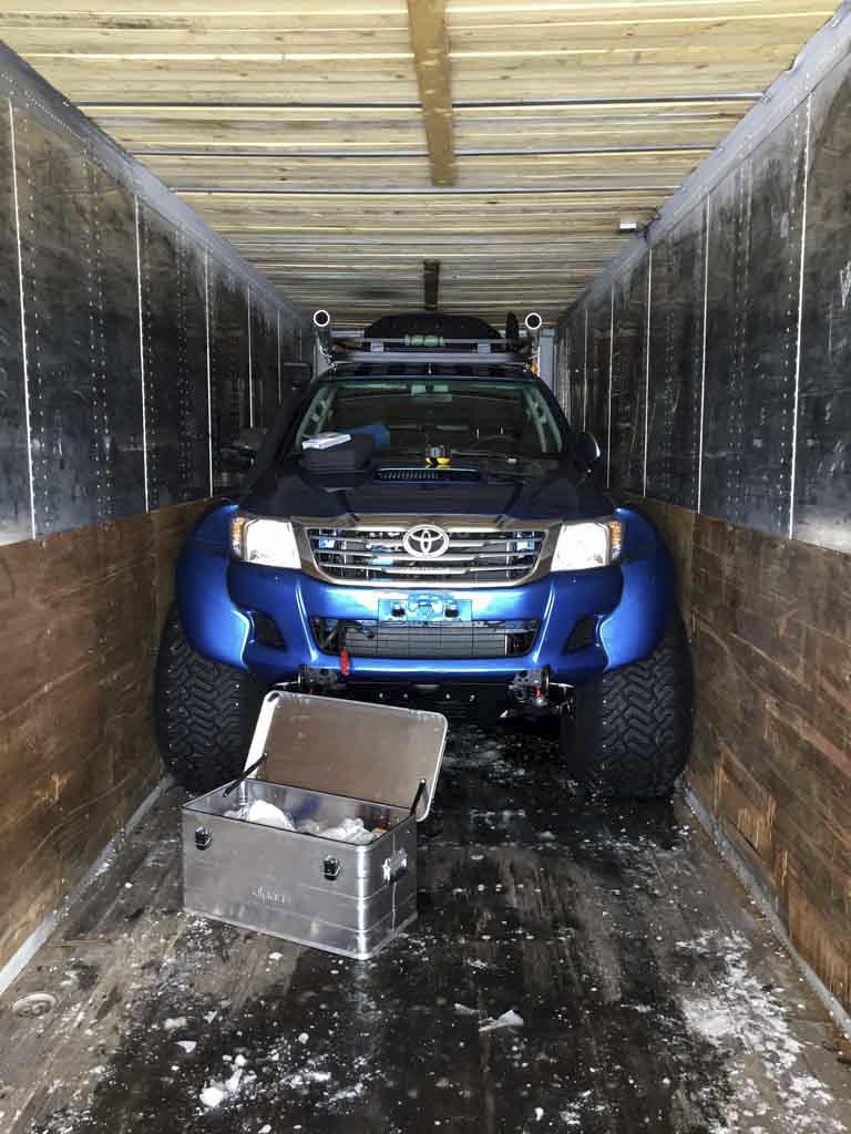 Stort bil med sexhjulsdrivning har parkerats i en container