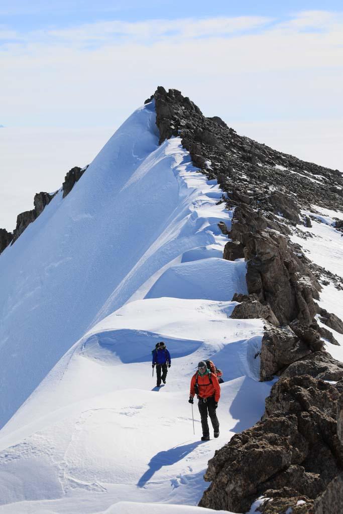 Två personer på en snöklädd bergskam