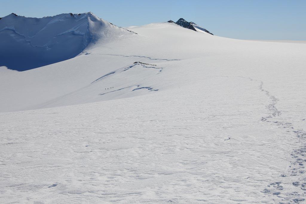 Fyra prickar skymtar långt bort på bergskammen