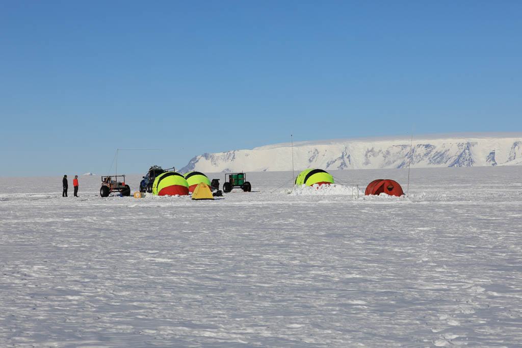Fältläger bestående av fyra tält och två bilar