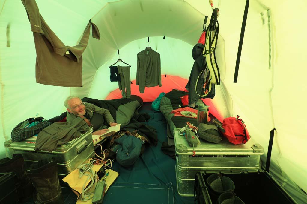 Man ligger på en tältsäng och runt omkring i tältet hänger massor av utrustning