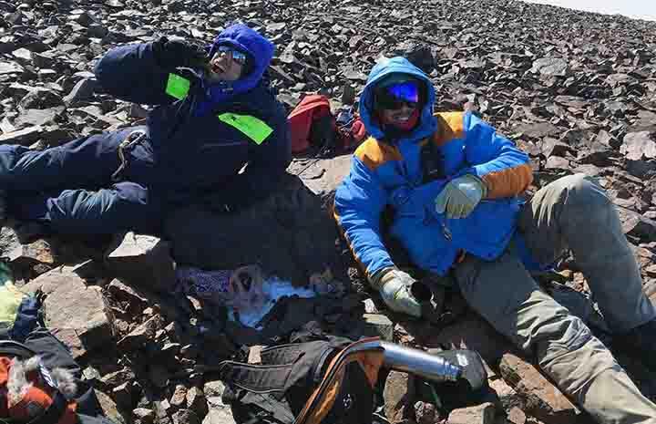 Två män ligger ner på stenarna och fikar